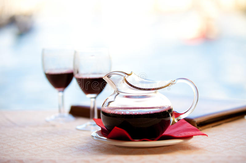 Carafe of Red wine. In Italy a Carafe a red wine - Chianti sits after being poured into glasses by the water under Rialto Bridge stock photo