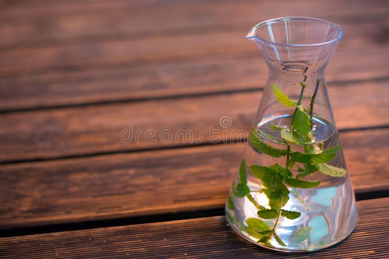 Carafe with water and mint-leafs. On wooden ground stock photos