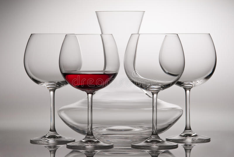 Carafe and wineglasses. Four wine glasses and carafe. One bottle is poured of red wine royalty free stock photo