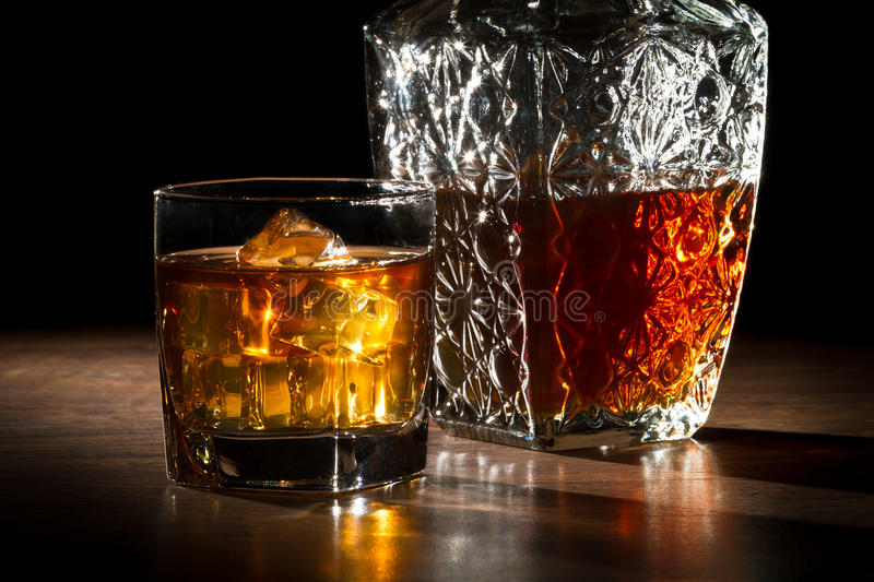 Carafer and glass with ice with whisky. On black background stock images