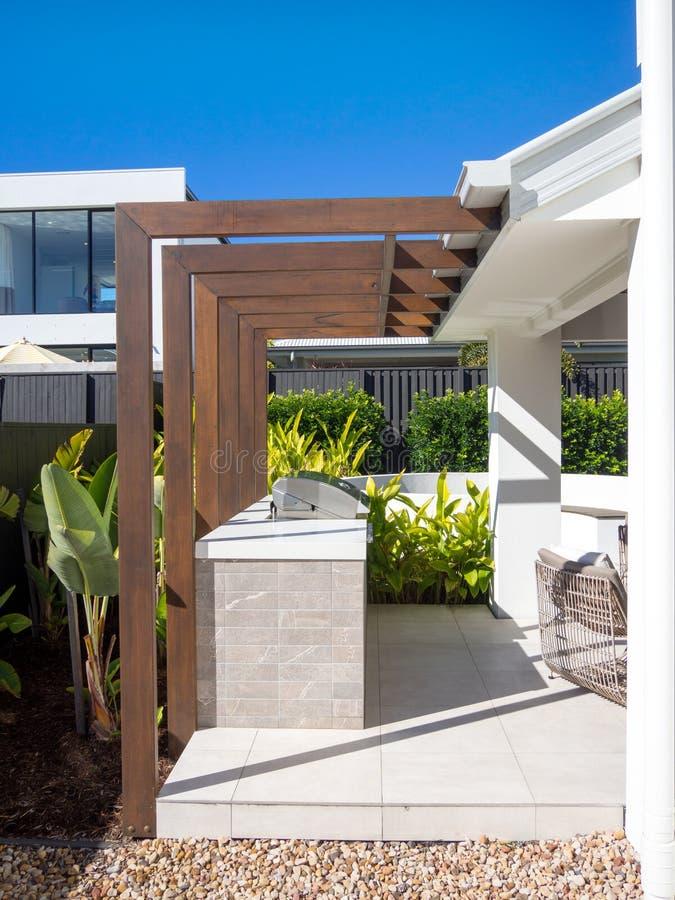 Caramanchão de madeira moderno e grade do BBQ no jardim exterior imagem de stock