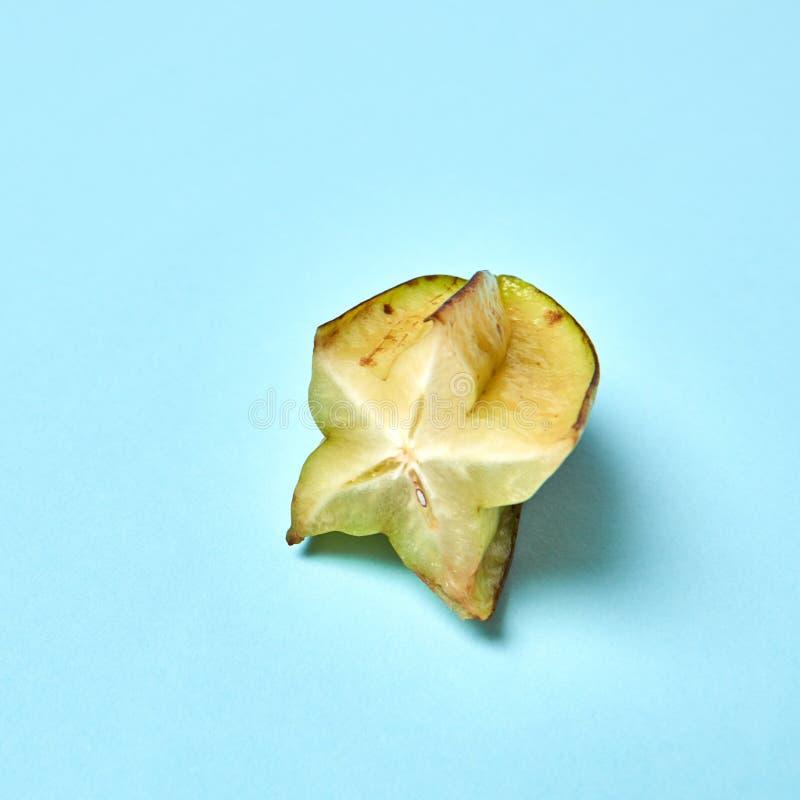 Carambola do fruto de estrela ou maçã de estrela tropical madura, starfruit em um fundo azul foto de stock
