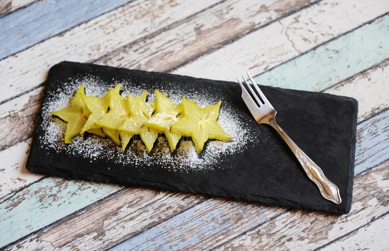 Carambola pieces served with icing sugar on a black slate plate. Carambola pieces served with icing sugar on black slate plate stock photo