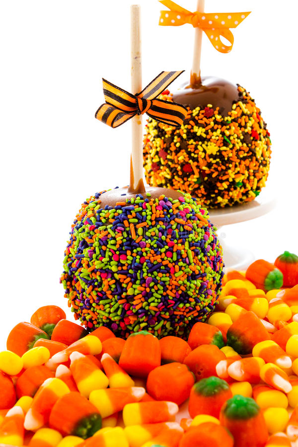 Caramel apple. Hand dipped caramel apple covered with multi color sprinkles royalty free stock photos