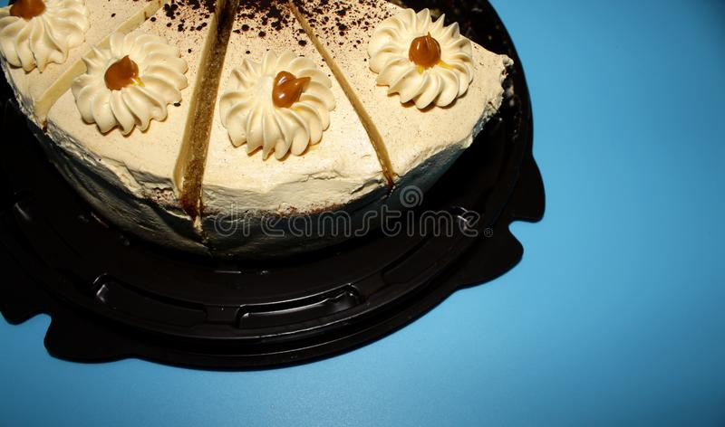 Caramel biscuit cake with cream on blue background. Brown round substrate - cake biscuit. Caramel with cream. Background blue royalty free stock images