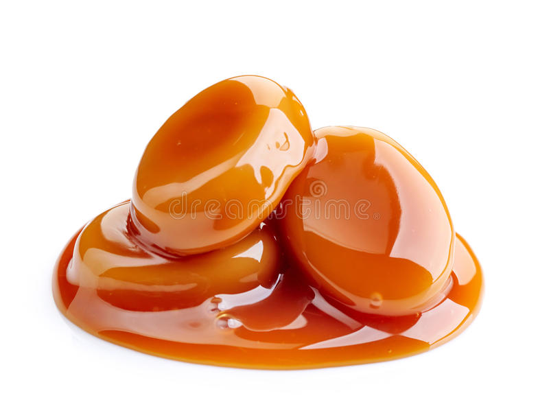 Caramel candies and sauce. On white background stock images