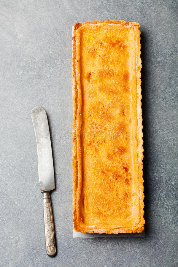 Caramel, creme brule tart. Grey stone background. Top view royalty free stock images