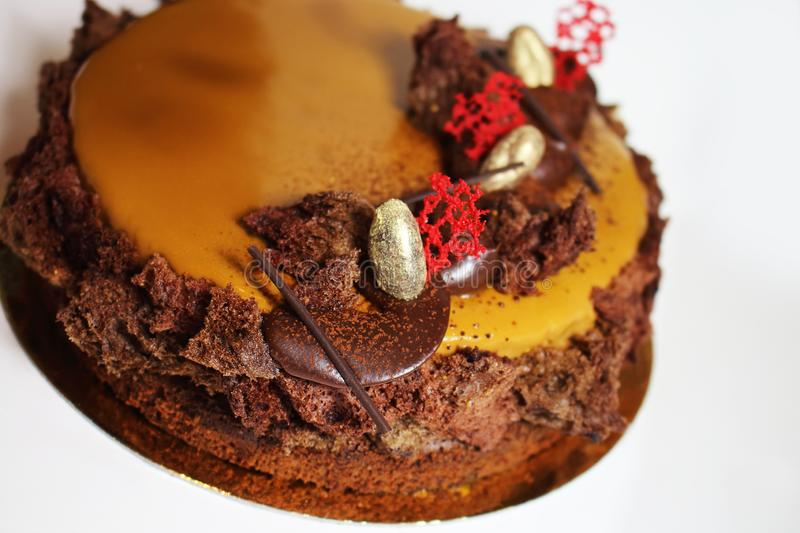 Caramel glazed round cake with silver almonds and chocolate ganache stock images