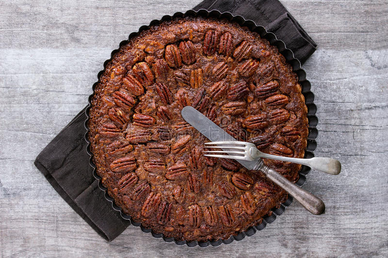 Caramel pecan pie. Homemade Big round caramel pecan pie in black iron forms, served with vintage cutlery on black textile napkin over gray textured background royalty free stock photography