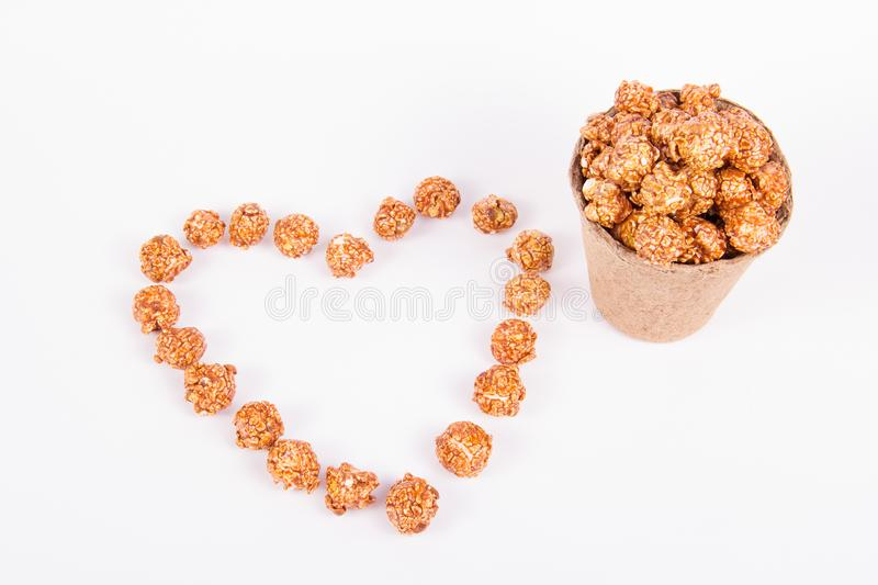 Caramel popcorn in a paper bucket and a heart made of popcorn. Romantic concept. stock photos