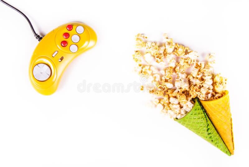 Caramel popcorn scattered on white background. Video game. Yellow GamePad. Yellow retro joystick royalty free stock photo