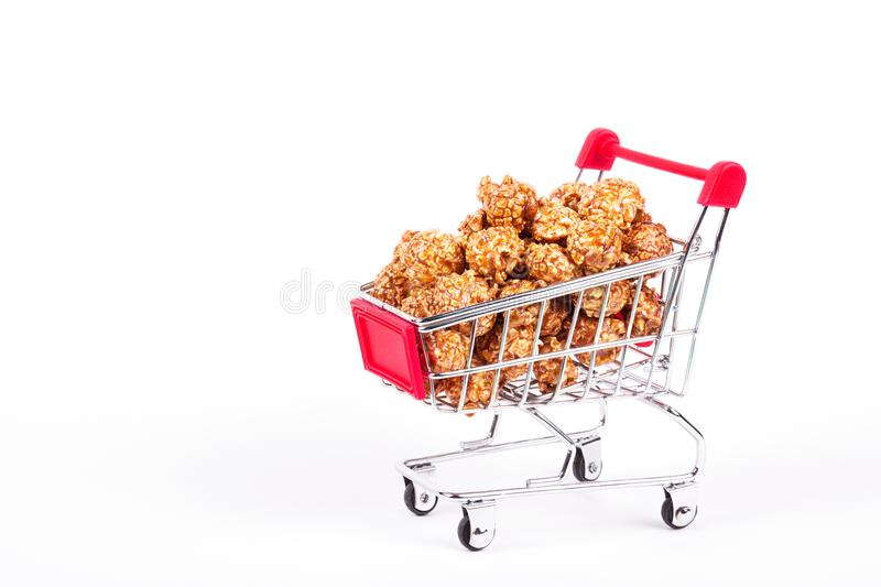 Caramel popcorn in a shopping trolley. Discount and sale concept. stock image