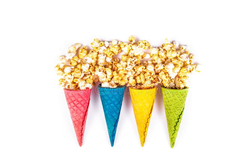 Caramel popcorn and waffle cones on white background. Scattered caramel popcorn. Bright sweets. Sweet corn and waffles. Copy space stock photography