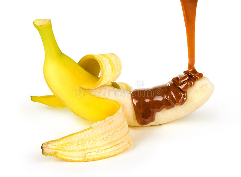 Caramel is poured on a banana. Isolated on a white background royalty free stock photo