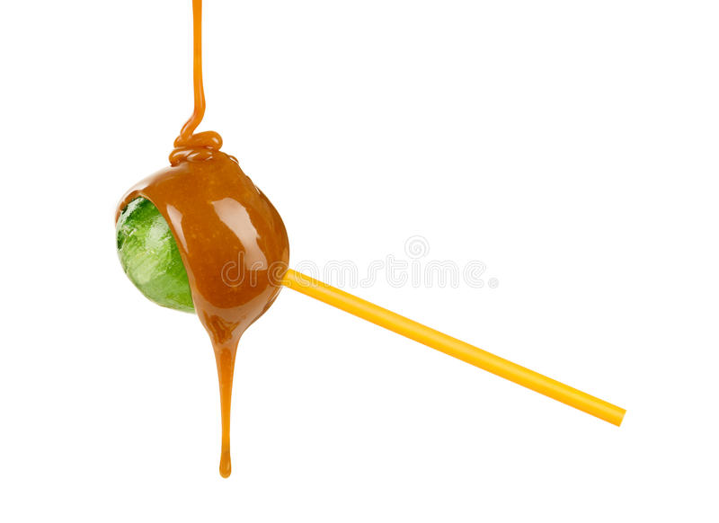 Caramel is poured on a lollipop. On a white background stock images