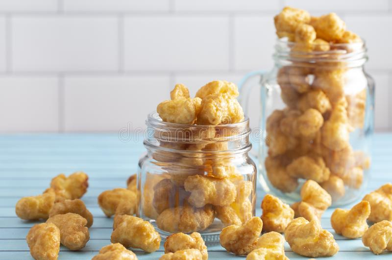 Caramel Puff Corn Popcorn in Glass Jars on a Blue Wood Counter. Caramel Puff Corn Popcorn in Glass Jars stock images