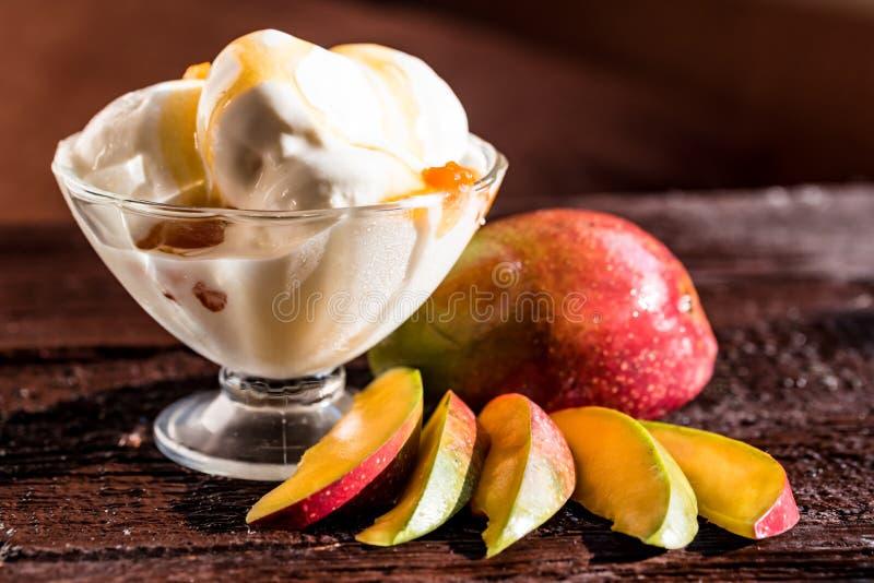 Caramel sauce ice cream and fresh mango fruit. Close up bowl with vanilla ice cream covered with caramel sauce and fresh mango fruit on wooden table. Selective royalty free stock photos