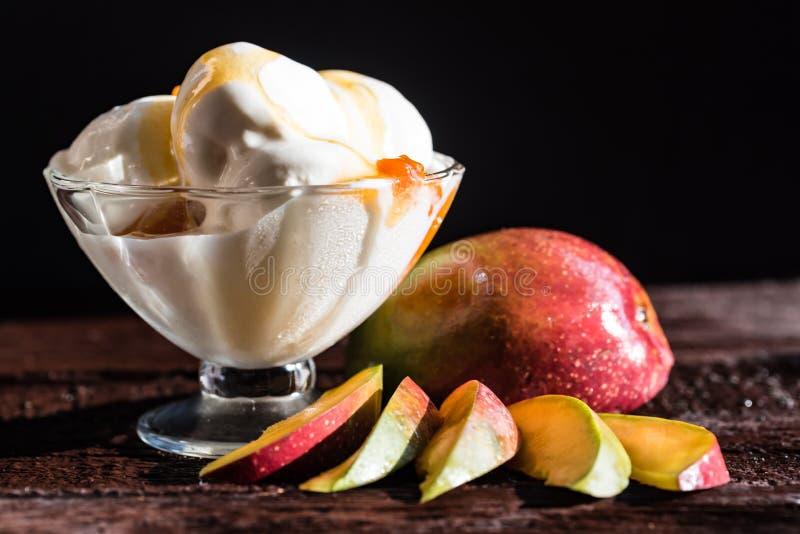 Caramel sauce ice cream and fresh mango fruit. Close up bowl with vanilla ice cream covered with caramel sauce and fresh mango fruit on dark background stock photos