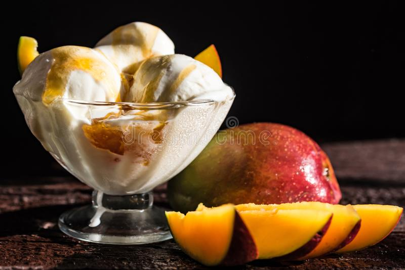 Caramel sauce ice cream and fresh mango fruit. Close up bowl with vanilla ice cream covered with caramel sauce and fresh mango fruit on dark background royalty free stock photo