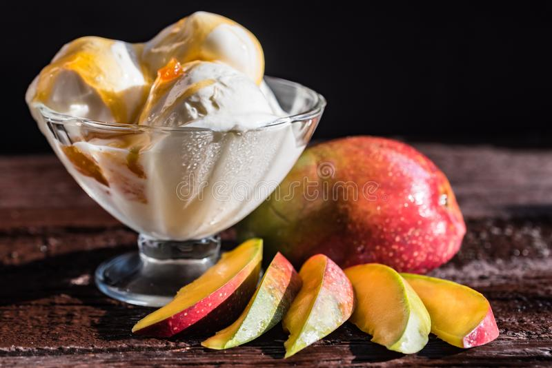 Caramel sauce ice cream and fresh mango fruit. Close up bowl with vanilla ice cream covered with caramel sauce and fresh mango fruit on dark background stock photography