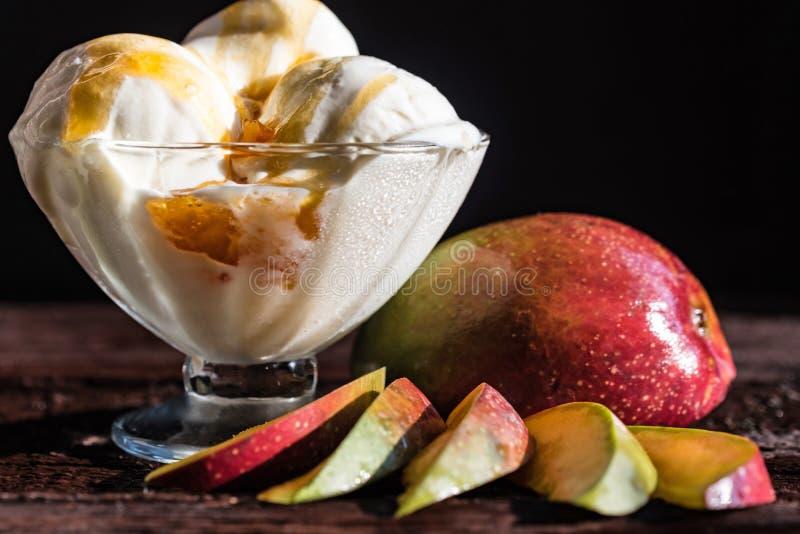 Caramel sauce ice cream and fresh mango fruit. Close up bowl with vanilla ice cream covered with caramel sauce and fresh mango fruit on dark background royalty free stock images