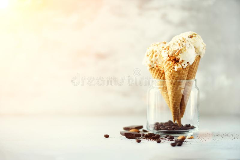Caramel sauce ice cream in waffle cone with coffee beans on grey stone background. Summer food concept, copy space. Healthy gluten free ice-cream. Banner royalty free stock photo