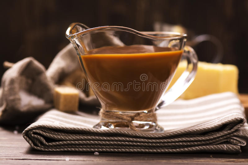 Caramel sauce and ingredients over grunge wooden background. royalty free stock images