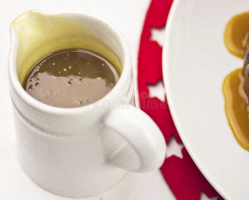 Caramel sauce. In jug on Christmas table royalty free stock photos