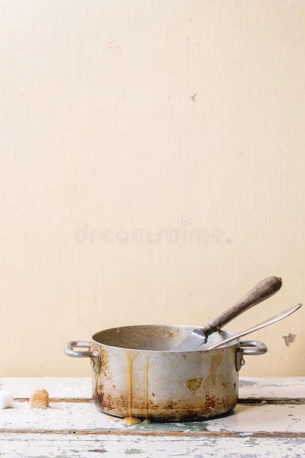 Caramel sauce. Old aluminum pan of homemade caramel sauce, served with spoons and sugar cubes over white wooden table stock image