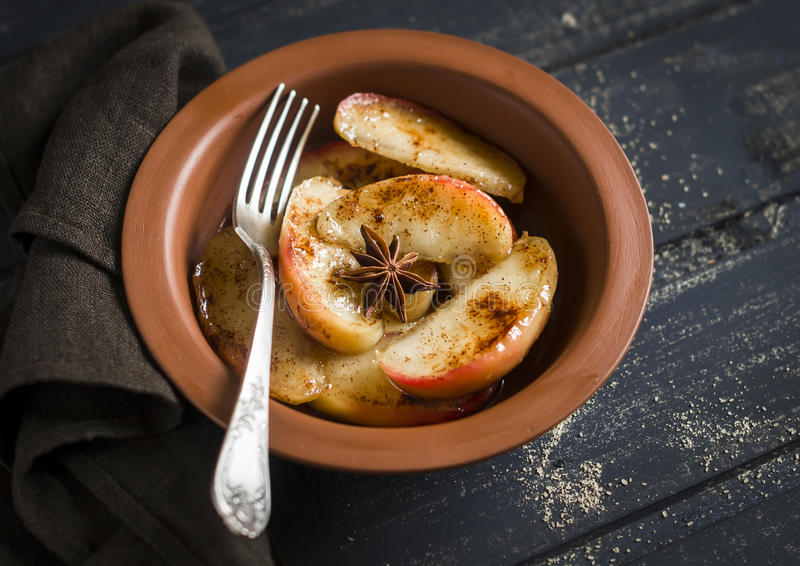 Caramelized яблоки с циннамоном и медом в блюде глины стоковое фото