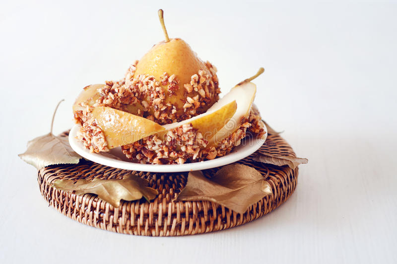 Caramelized pear dipped with peanuts decorated with golden leave. Caramelized pear dipped with chopped peanuts decorated with golden leaves royalty free stock photography