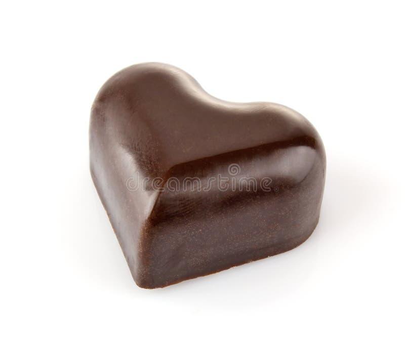 Caramella di cioccolato nel cuore di apparenza immagini stock