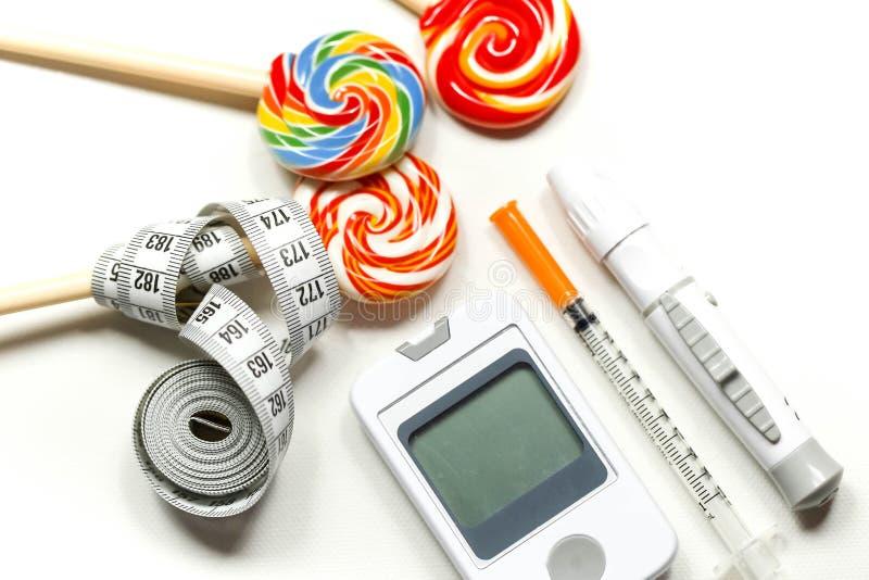 Caramella dolce con la siringa dell'insulina, lancetta, striscia test, metro del glucosio immagini stock