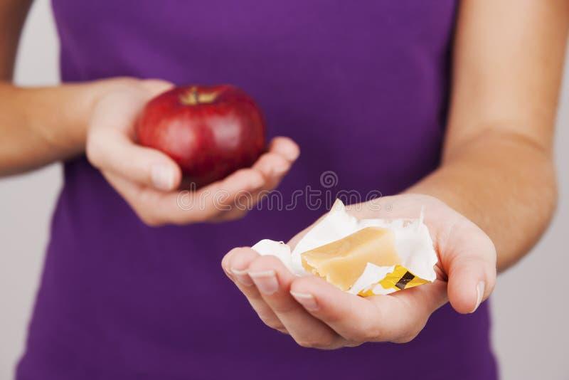 Caramella e mela della tenuta della giovane donna immagini stock libere da diritti