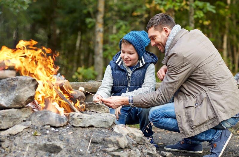 Caramella gommosa e molle di torrefazione del figlio e del padre sopra fuoco di accampamento fotografia stock
