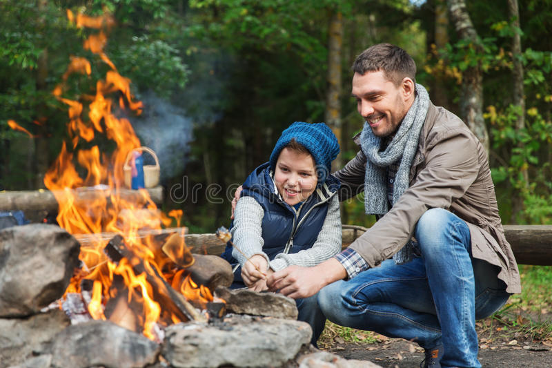 Caramella gommosa e molle di torrefazione del figlio e del padre sopra fuoco di accampamento immagine stock libera da diritti