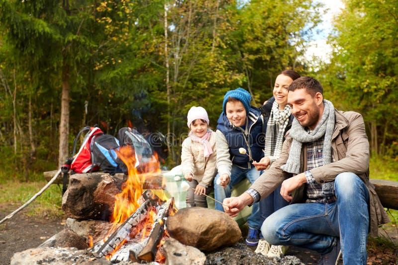 Caramella gommosa e molle felice di torrefazione della famiglia sopra fuoco di accampamento fotografia stock libera da diritti