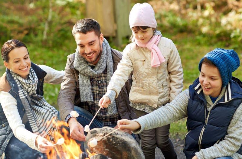 Caramella gommosa e molle felice di torrefazione della famiglia sopra fuoco di accampamento immagine stock libera da diritti