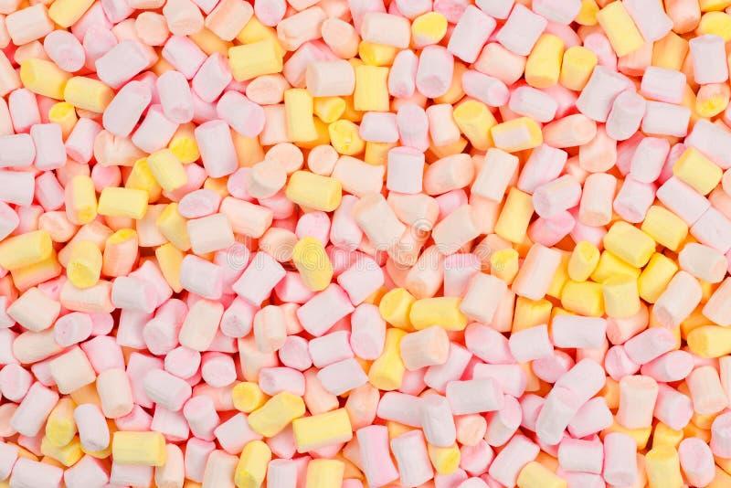 Caramella gommosa e molle Fondo del rosa e di mini caramelle gommosa e molle variopinte gialle fotografia stock libera da diritti