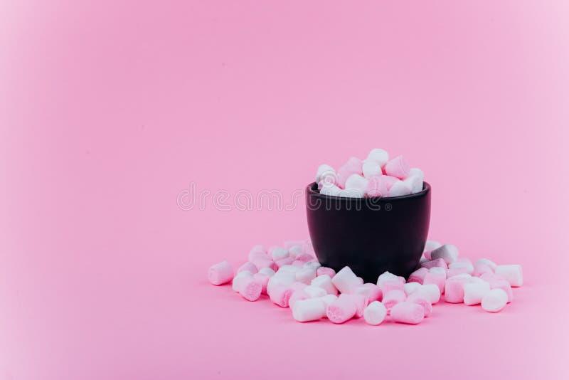 Caramella gommosa e molle pastello in una tazza su un fondo rosa fotografia stock