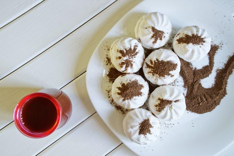 Caramella gommosa e molle - zefiro, spolverato con di pepita di cioccolato, bugie in un piatto su un fondo di legno bianco Vicino fotografia stock