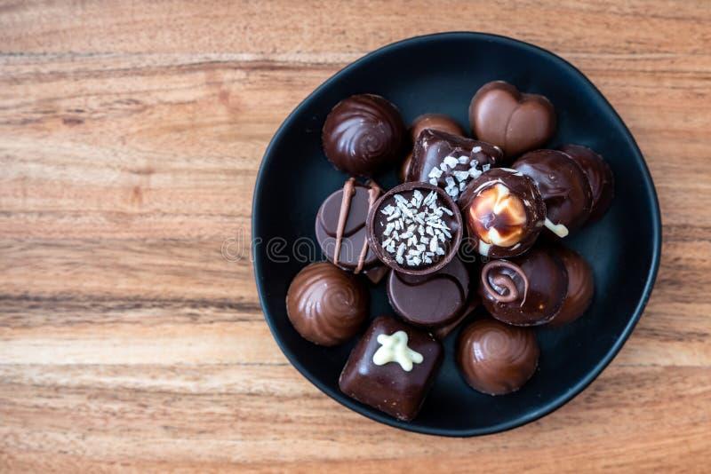 Caramella operata assortita di cioccolato fondente e del latte su una banda nera rustica su un fondo di legno fotografie stock libere da diritti