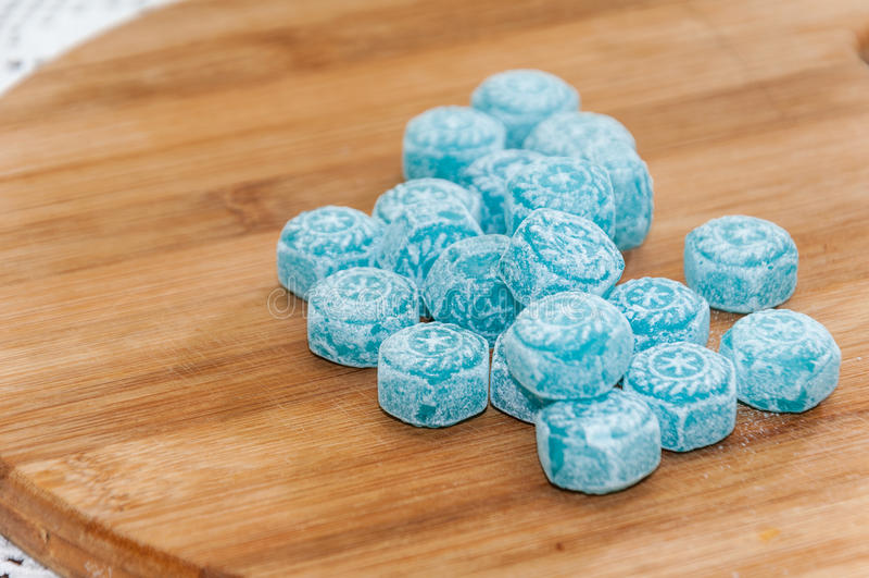 Caramelle alla menta blu sul bordo di legno immagini stock