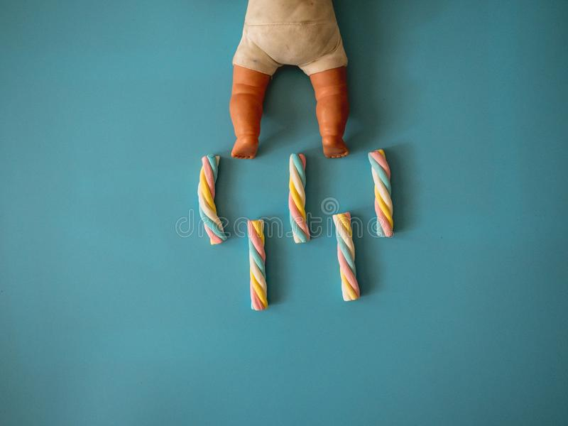 Caramelle con forma della nuvola su un fondo degli azzurri accanto ad un giocattolo del bambino fotografia stock