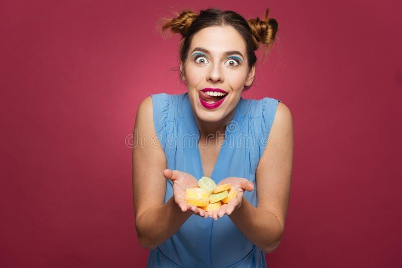 Caramelle della gelatina della tenuta della donna e lingua emozionanti divertenti di rappresentazione immagini stock libere da diritti