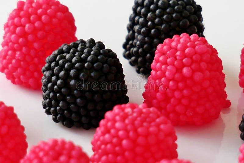 Caramelle della gelatina sotto forma di lamponi, rosso e nero su un fondo bianco immagine stock libera da diritti