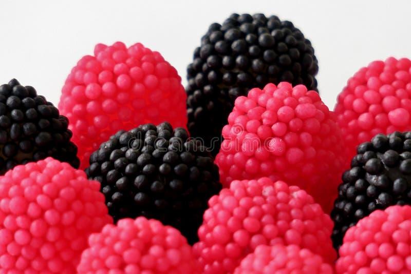 Caramelle della gelatina sotto forma di lamponi, rosso e nero su un fondo bianco immagini stock