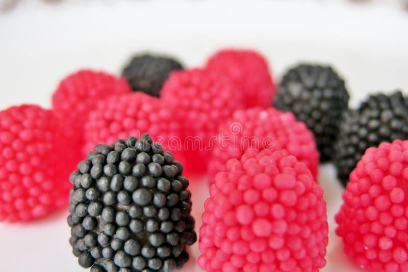Caramelle della gelatina sotto forma di lamponi, rosso e nero su un fondo bianco immagine stock