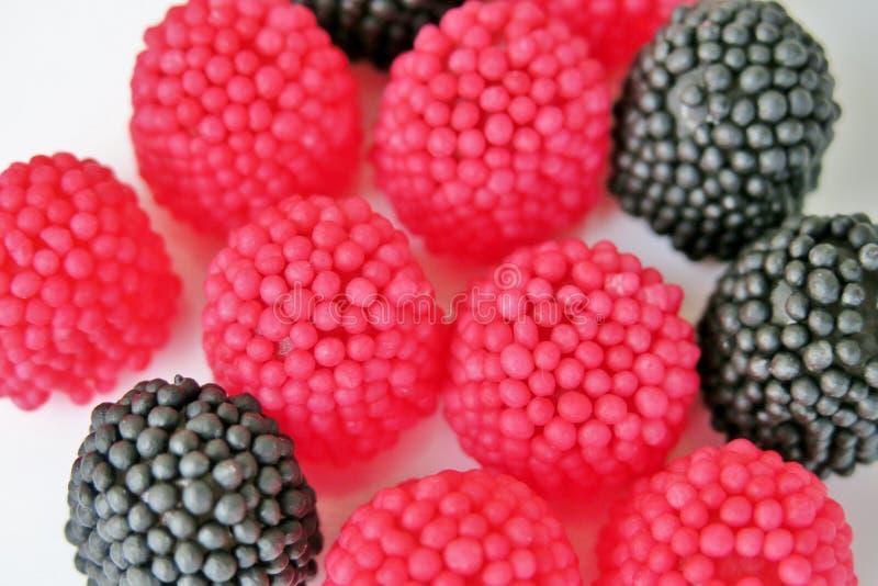 Caramelle della gelatina sotto forma di lamponi, rosso e nero su un fondo bianco fotografia stock libera da diritti