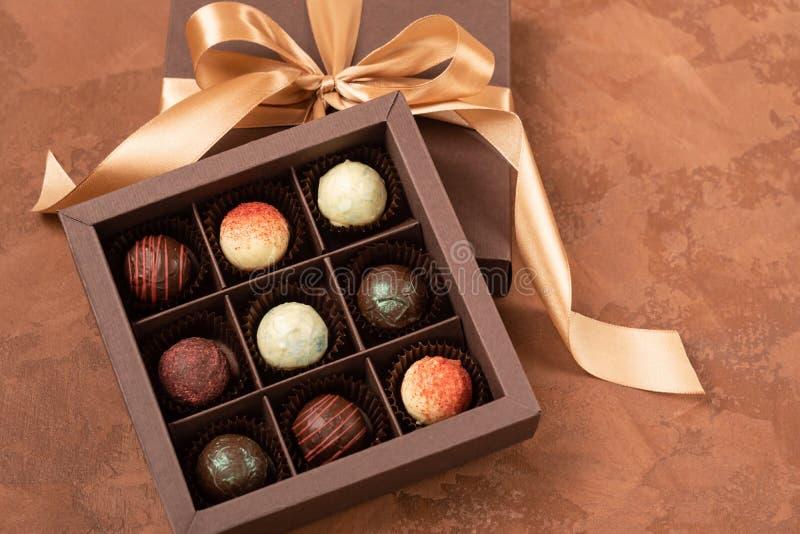 Caramelle di cioccolato in una scatola di carta scura con un nastro del raso su un fondo strutturato marrone Disposizione piana C fotografia stock